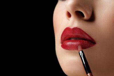 Plakat zdjęcia makro zbliżenie z pędzla szminki i naturalne wielkie czerwone usta młodej kobiety na czarnym tle