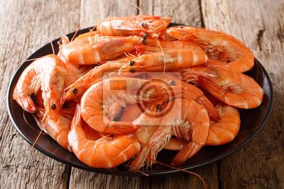 Plakat Zdrowa dieta: zbliżenie gotowanych krewetek dzikiego tygrysa na talerzu na stole. poziomy