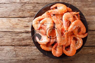 Plakat Zdrowa dieta: zbliżenie gotowanych krewetek dzikiego tygrysa na talerzu na stole. Poziomy widok z góry