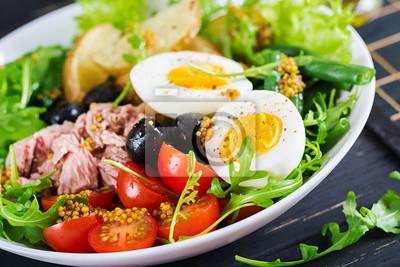 Zdrowa obfita sałatka z tuńczyka, fasolki szparagowej, pomidorów, jajek, ziemniaków, czarnych oliwek z bliska w misce na stole. Sałatka Nicoise. Kuchnia francuska.