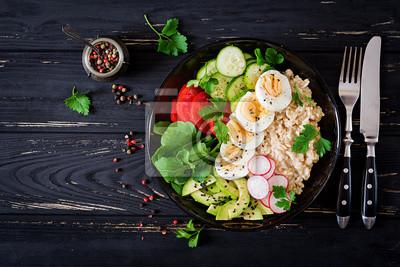 Zdrowa sałatka ze świeżych warzyw - pomidory, awokado, ogórek, rzodkiewka, jajko, rukola i płatki owsiane na misce. Dietetyczne jedzenie. Leżał płasko. Widok z góry