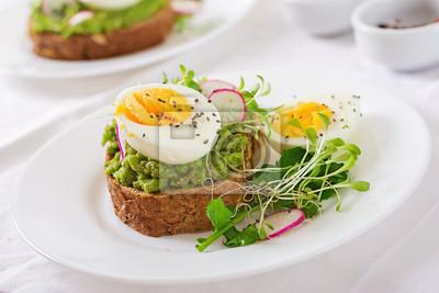 Zdrowe jedzenie. Śniadanie. Avocado jajeczna kanapka z całym zbożowym chlebem na białym drewnianym tle.