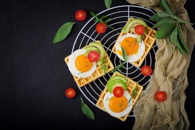 Zdrowe śniadanie - gofry, jajka, awokado, pomidory i zioła. Płaskie leże. Widok z góry