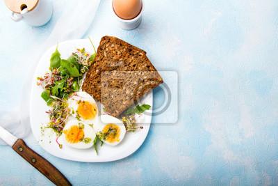 Plakat Zdrowe śniadanie: jajka na twardo, kiełki świeżej rzodkiewki, rukola i ciemne pieczywo pełnoziarniste z sosem ziołowym, na niebieskim tle