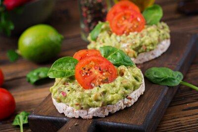 Zdrowe śniadanie. Ściska chrupiącego chleb z guacamole i pomidorami na drewnianym tle.