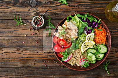 Zdrowy obiad. Budda miska obiad z grillowanym kurczakiem i quinoa, pomidor, guacamole, marchew, czerwona kapusta, ogórek i rukolą na drewniane tła. Płaskie leżało. Widok z góry