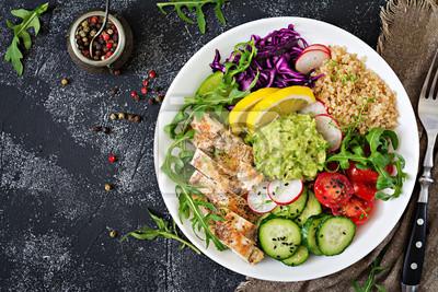 Zdrowy obiad. Obiad miski Buddy z grillowanym kurczakiem i quinoa, pomidor, guacamole, czerwona kapusta, ogórek i arugula na szarym tle. Płaskie leżało. Widok z góry