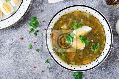 Zielona zupa szczawiowa z jajkami. Menu letnie. Zdrowe jedzenie. Płaskie leżało. Widok z góry