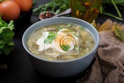 Zielona zupa szczawowa w niebieskiej misce.