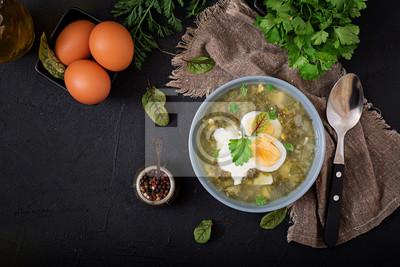 Zielona zupa szczawowa w niebieskiej misce. Płaskie leże. Widok z góry