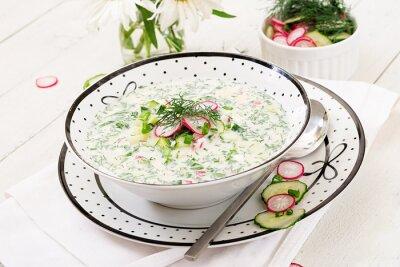 Zimna polewka z świeżymi ogórkami, rzodkwie z jogurtem w pucharze na drewnianym tle. Tradycyjne rosyjskie jedzenie - okroshka. Posiłek wegetariański.