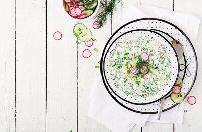 Zimna polewka z świeżymi ogórkami, rzodkwie z jogurtem w pucharze na drewnianym tle. Tradycyjne rosyjskie jedzenie - okroshka. Posiłek wegetariański. Widok z góry. Płaskie leżało
