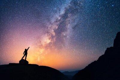 Plakat Złapać gwiazdę. Osoba stoi obok Drogi Mlecznej wskazując na jasne gwiazdy.