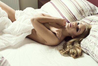 Plakat zmysłowa naga dziewczyna leży na łóżku
