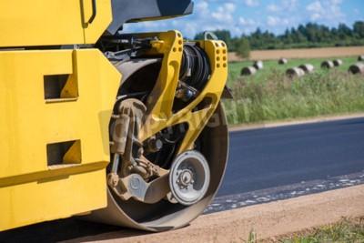 Żółty ciężki wibracyjny rolownik przy asfaltowymi bruk pracuje. Naprawa dróg w mieście. Pracownicy drogowi naprawia autostrady autostradę na pogodnym letnim dniu. Ciężkie maszyny, ładowarki i ciężarów