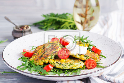 Zucchini pancakes with corn and sour cream served arugula, tomatoes salad.