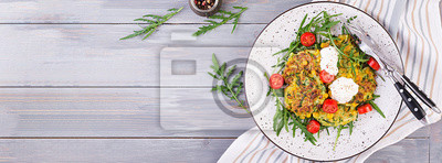 Zucchini pancakes with corn and sour cream served arugula, tomatoes salad. Banner. Top view