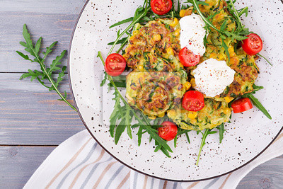 Zucchini pancakes with corn and sour cream served arugula, tomatoes salad. Top view