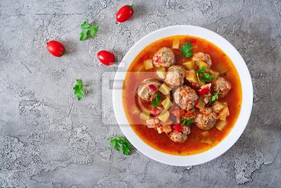 Zupa pomidorowa gorącego gulaszu z klopsikami i warzywami zbliżenie w misce na stole. Zupa Albondigas, hiszpańskie i meksykańskie jedzenie. Widok z góry. Leżał płasko