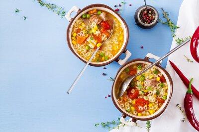 Zupa z małym makaronem, warzywami i kawałkami mięsa w misce na niebieskim stole. Włoskie jedzenie. Leżał płasko