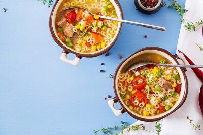 Zupa z małym makaronem, warzywami i kawałkami mięsa w misce na niebieskim stole. Włoskie jedzenie. Widok z góry. Leżał płasko