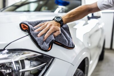 Tapeta A man cleaning car with microfiber cloth, car detailing (or valeting) concept. Selective focus.