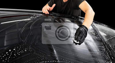 Tapeta A man cleaning car with microfiber cloth. Car detailing or valeting concept. Selective focus. Car detailing. Cleaning with sponge. Worker cleaning. Car wash concept solution to clean
