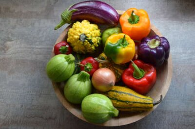 Tapeta A wooden bowl with fresh organic autumn vegetables: zucchinis, pumpkins, red, orange and purple paprika, onions, eggplant