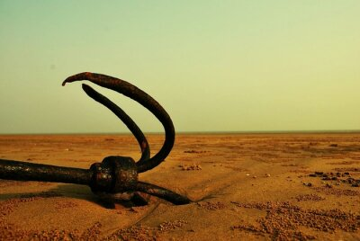 Abandoned Rusty Metal Anchor In Sand