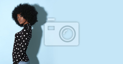 Tapeta Afro-american model in original black golf with white dots isolated on blue background.