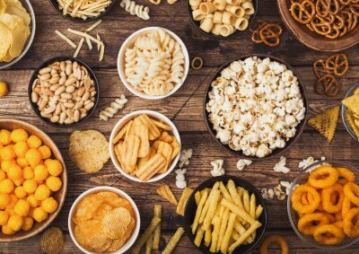 Tapeta All classic potato snacks with peanuts, popcorn and onion rings and salted pretzels in bowl plates on wooden background. Twirls with sticks and potato chips and crisps with nachos and cheese balls.