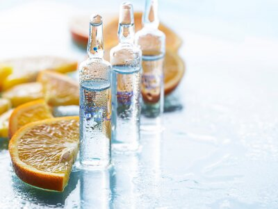 Tapeta Ampoule with vitamin C for injection and fresh citrus fruits. Natural cosmetics concept. Organic cosmetics.