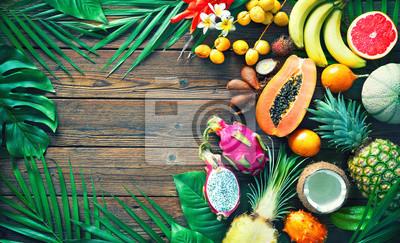 Tapeta Asortyment tropikalne owoc z liśćmi drzewka palmowe i egzotyczne rośliny na ciemnym drewnianym tle