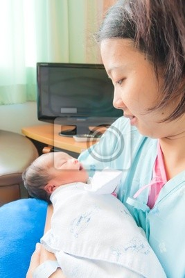 Azjatyckich kobiet noworodka w ramionach matki pionowych