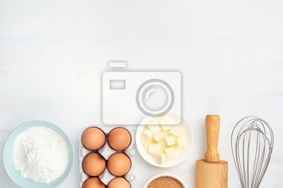 Tapeta Baking ingredients and kitchen utensils on white background. Chicken eggs, butter, sugar, flour, rolling pin and whisker. Cooking, baking, pastry or cookie dough ingredients
