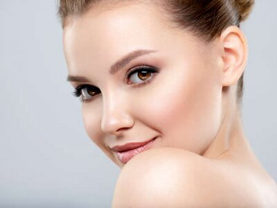 Tapeta Beautiful face of young smiling woman with clean fresh skin - isolated.  Young white happy woman with a clean skin.