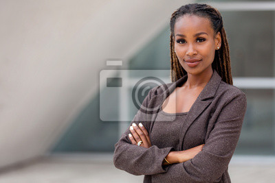 Tapeta Beautiful female african american business woman CEO in a suit at the workplace, standing confidently with arms folded