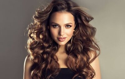 Tapeta Beautiful model with long, dense, curly hairstyle and vivid makeup. Bold and dazzling look of beautiful lady. Hairdressing art, hair care and beauty products.