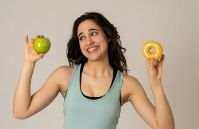 Tapeta Beautiful young fit latin woman tempted having to make choice; apple and doughnut, healthy or unhealthy food. Fitness and nutrition healthy lifestyle and Diet concept. Studio shot with copy space.
