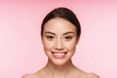 Tapeta Beauty portrait of a beautiful smiling young topless brunette woman standing isolated over pink background