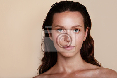 Tapeta Beauty woman portrait. Beautiful spa model girl with perfect fresh clean skin. Youth and skin care concept. Beige background. Nude makeup