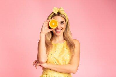 Tapeta Blonde girl holding orange slice next to eye