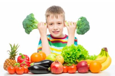 Tapeta Boy 10 years old with broccoli and a bunch of vegetables and fruits posing in the studio isolated on white background
