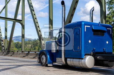 Bright blue classic American idol big rig bonnet semi truck tractor running on the arched truss bridge at sunny day