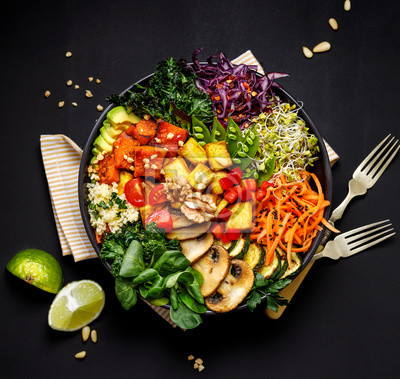 Tapeta Buddha bowl of mixed vegetables, tofu cheese and groat on a black background, top view. Gourmet and nutritious vegan meal. Healthy eating concept