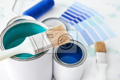 Tapeta Cans of paint with brush on table, closeup