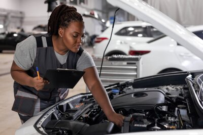 Tapeta car service, job and profession concept. young african female worker in gray uniform with clipboard and pen writing over auto repair shop on background