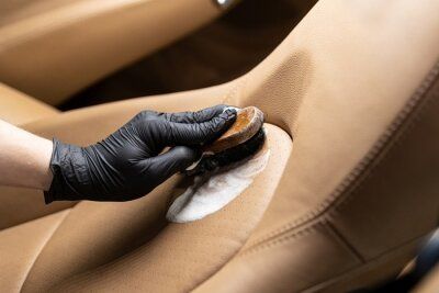 Tapeta Cleaning leather car seat and upholstery with brush. Car detailing