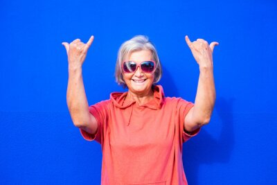 Tapeta close up and portrait of funny and crazy senior or mature woman doing surfing sign and smililing looking at the camera with blue background - pensioner wearing red clothes and sunglasses happy people