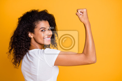Tapeta Close-up profile side view portrait of her she nice attractive lovely brunet cheerful wavy-haired girl showing strong muscles isolated over bright vivid shine vibrant yellow color background